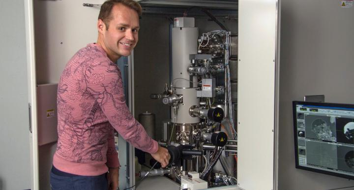 Pierre Haenecour, the study's lead author, is pictured with one of the ultra-high-resolution electron microscopes used to obtain chemical and microstructural information about the stardust grain. (Photo: Maria Schuchardt/University of Arizona)